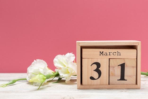 Calendário de forma de cubo de madeira para 31 de março na mesa de madeira