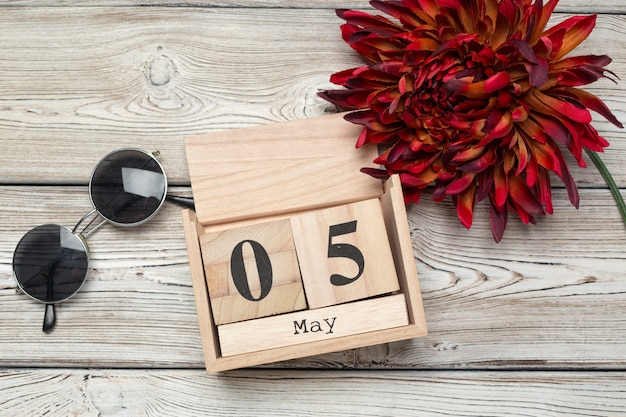 Calendário de forma de cubo de madeira para 5 de maio na mesa de madeira