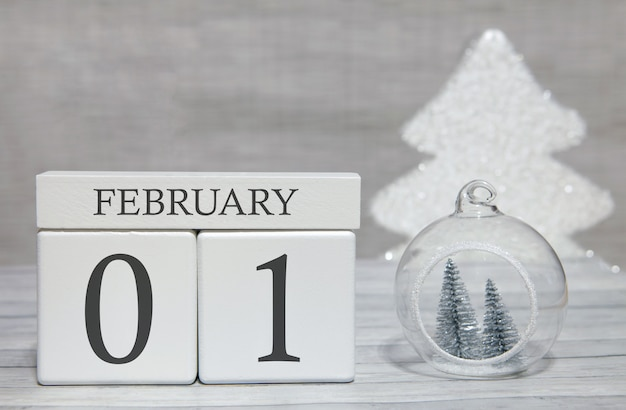 Calendário de forma de cubo para 1 de fevereiro na superfície de madeira e fundo claro
