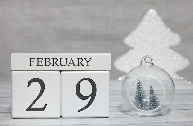 Calendário de forma de cubo para 29 de fevereiro na superfície de madeira e luz de fundo
