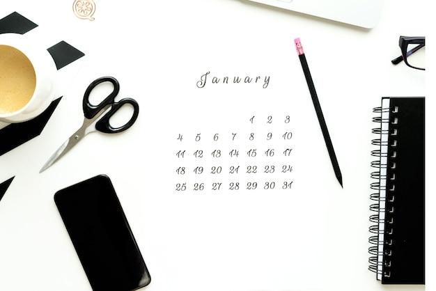 Calendário de janeiro na mesa plana ley branca com uma xícara de café e um notebook.