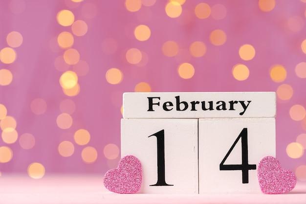 Calendário de madeira 14 de fevereiro na vista frontal do fundo rosa bokeh