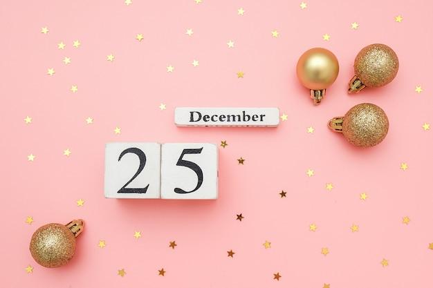Calendário de madeira, 25 de dezembro, bolas douradas de natal e confetes estrelas na parede rosa. conceito de feliz natal.