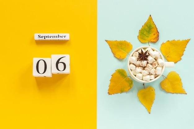 Calendário de madeira 6 de setembro, xícara de chocolate com marshmallows e folhas de outono amarelas sobre fundo azul amarelo.