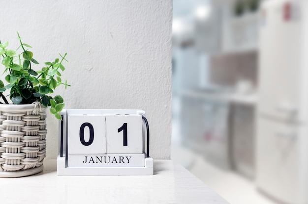 Calendário de madeira branco com preto palavra de 1 de janeiro na mesa no quarto branco