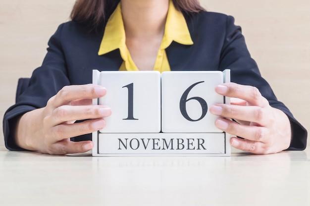 Calendário de madeira closeup com palavra de 16 de novembro preto na mão de mulher de trabalho turva