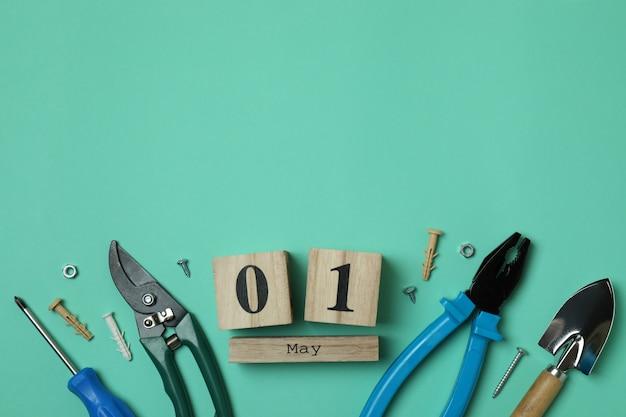 Calendário de madeira com 1 de maio e ferramentas no fundo da casa da moeda
