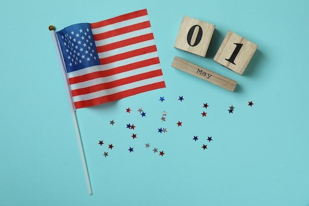 Calendário de madeira com 1 de maio, glitter e bandeira americana em azul