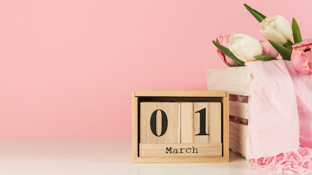 Calendário de madeira com 1 de março perto da caixa com tulipas e lenço na mesa contra fundo rosa