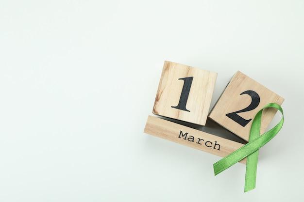 Calendário de madeira com 12 de março e fita de consciência verde sobre fundo branco