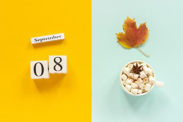 Calendário de madeira com 8 de setembro, xícara de chocolate com marshmallows e folhas amarelas de outono