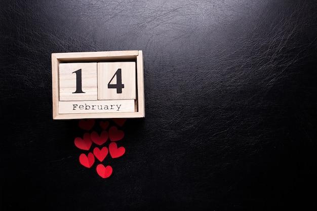 Calendário de madeira com a inscrição em 14 de fevereiro e com pequenas corações em um fundo preto e isolado.