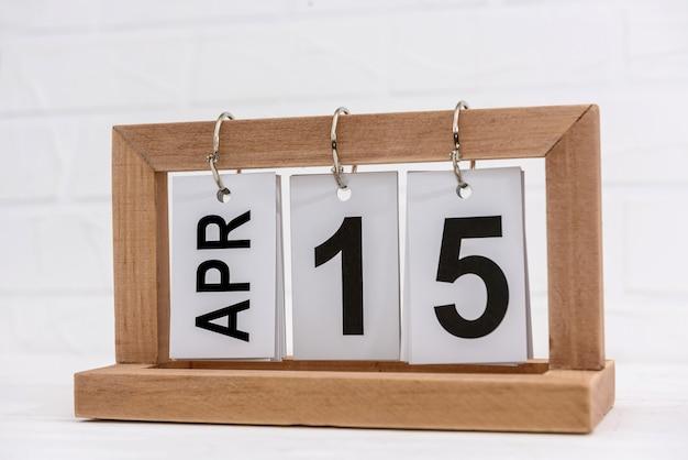 Calendário de madeira com data 15 de abril, dia do imposto