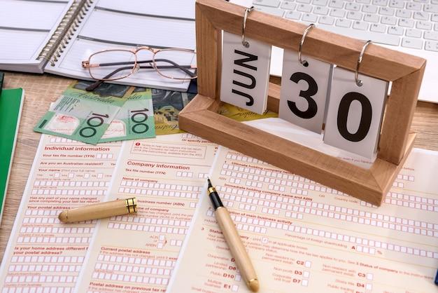 Calendário de madeira com declaração fiscal australiana na mesa