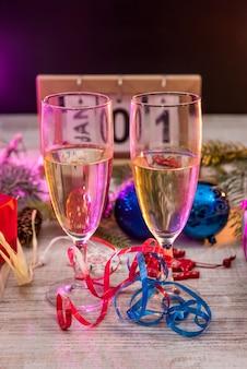 Calendário de madeira com taças de champanhe e decorações de ano novo na mesa de madeira