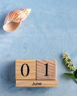 Calendário de madeira de 1º de junho em uma superfície azul com flores brancas