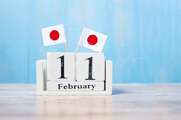 Calendário de madeira de 11 de fevereiro com bandeiras japonesas em miniatura.