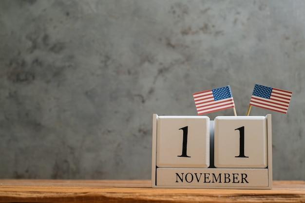Calendário de madeira de 11 de novembro com bandeiras americanas em miniatura. conceitos de celebração do dia mundial do veterano