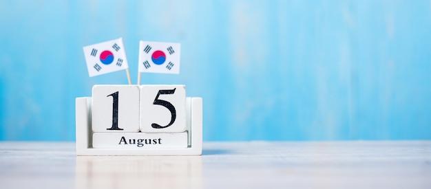 Calendário de madeira de 15 de agosto com bandeiras em miniatura da república da coréia. dia da independência, dia da libertação nacional da coréia, dia da nação feriado e conceitos de feliz celebração
