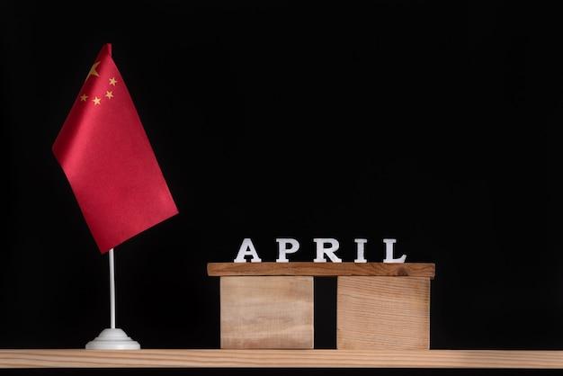 Calendário de madeira de abril com bandeira chinesa em fundo preto. férias da china em abril.