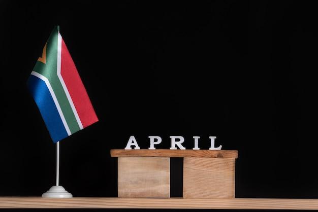 Calendário de madeira de abril com bandeira rsa em fundo preto. datas da áfrica do sul em abril.