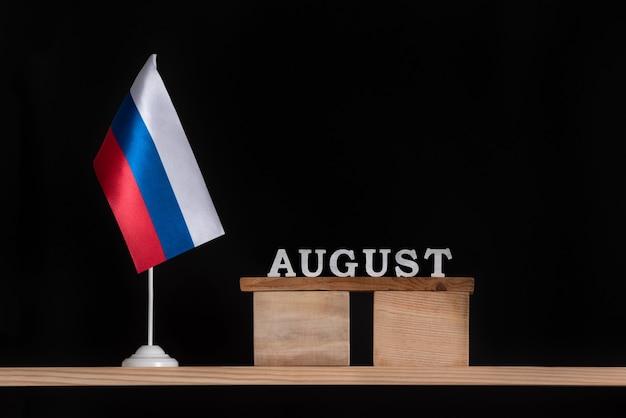 Calendário de madeira de agosto com bandeira russa em fundo preto. datas na rússia em agosto.