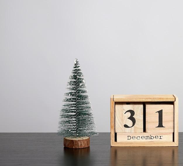 Calendário de madeira de cubos com a data de 31 de dezembro e a árvore verde