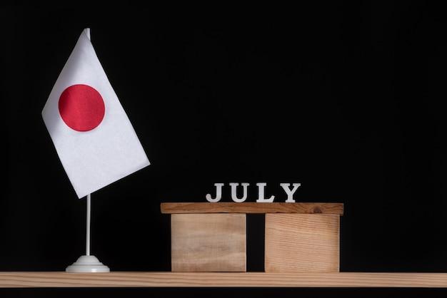 Calendário de madeira de julho com a bandeira do japão em fundo preto.