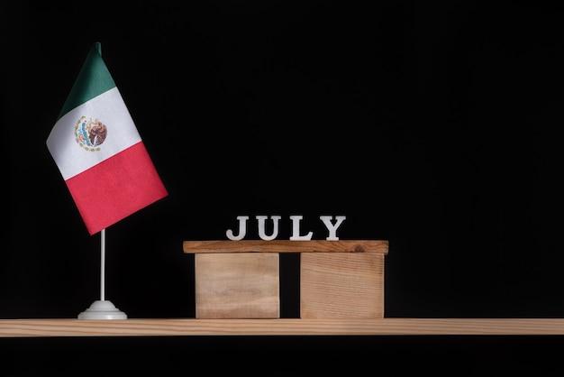 Calendário de madeira de julho com a bandeira do méxico em fundo preto.