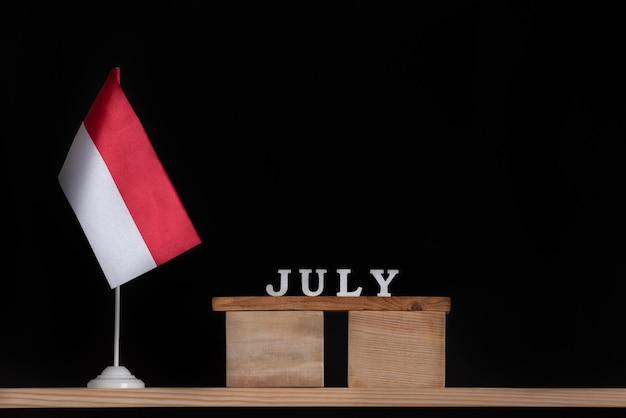 Calendário de madeira de julho com bandeira polonesa em fundo preto. férias da polônia em julho.