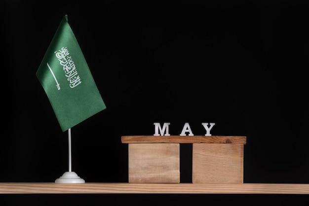 Calendário de madeira de maio com a bandeira da arábia saudita em fundo preto. datas da arábia saudita em maio.