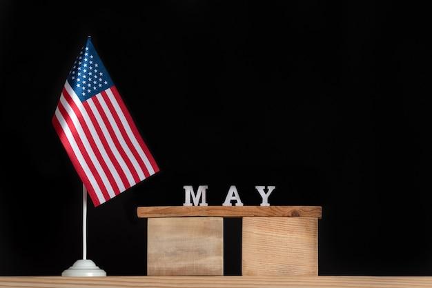 Calendário de madeira de maio com a bandeira dos eua em fundo preto. férias dos estados unidos da américa em maio.