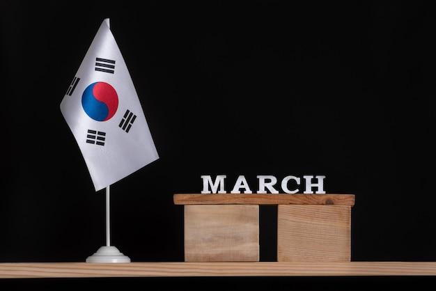 Calendário de madeira de março com a bandeira da coreia do sul, fundo preto. férias da coreia do sul em março.