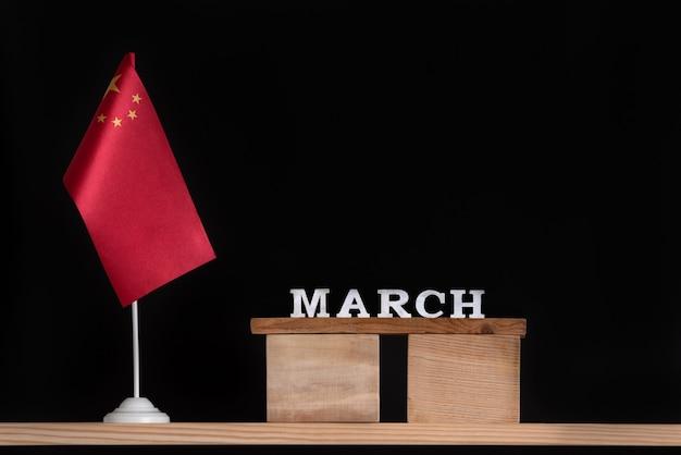 Calendário de madeira de março com bandeira chinesa em fundo preto. férias da china em março.