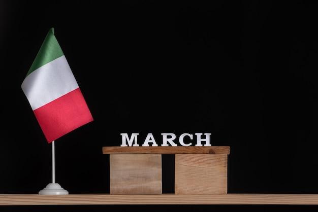 Calendário de madeira de março com bandeira italiana em fundo preto. datas na itália em março.
