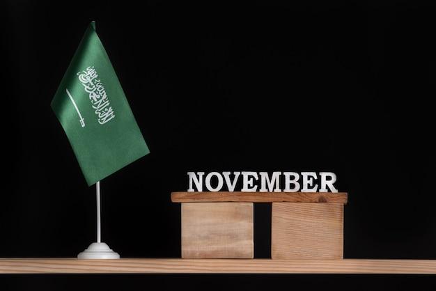 Calendário de madeira de novembro com a bandeira da arábia saudita em fundo preto. datas da arábia saudita em novembro.
