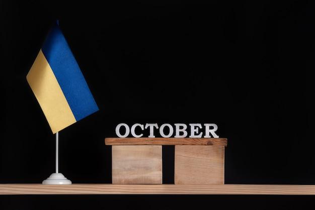 Calendário de madeira de outubro com bandeira ucraniana em fundo preto. datas na ucrânia em outubro.