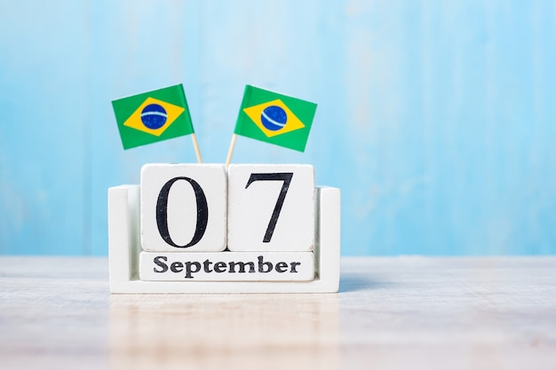 Calendário de madeira do dia 7 de setembro com bandeiras do brasil em miniatura.
