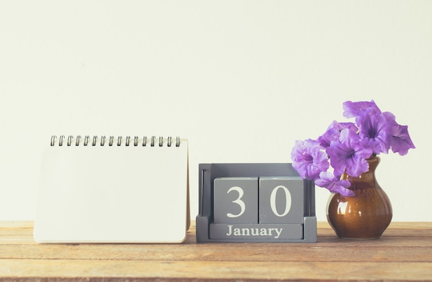 Calendário de madeira do vintage para o dia 30 de janeiro na tabela de madeira com espaço vazio do livro de nota para o texto.