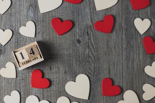 Calendário de madeira e corações de madeira, brancos e vermelhos colocados em um piso de madeira cinza, vista superior e cópia espaço, tema do dia dos namorados