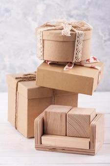 Calendário de madeira em branco vazio e caixas de presente kraft na mesa branca. zombe de ideias de celebração, venda ou feriado