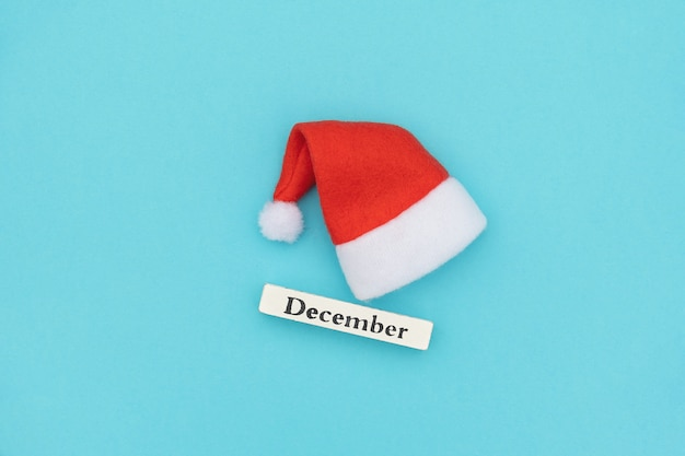 Calendário de madeira inverno mês dezembro e chapéu de papai noel em papel azul