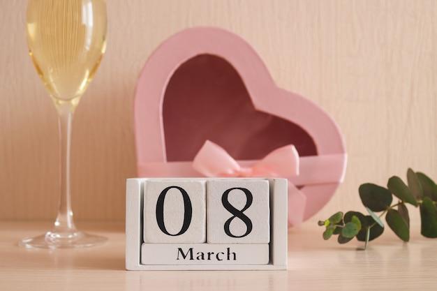 Calendário de madeira march, uma taça de champanhe e uma caixa de presente em forma de coração