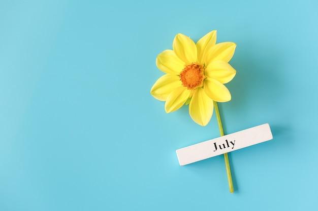 Calendário de madeira, mês de verão de julho e flor amarela