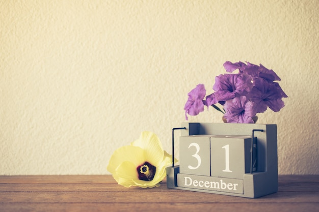 Calendário de madeira vintage, definido no dia 31 de dezembro com o conceito de flor feliz ano novo