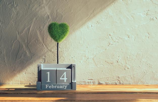 Calendário de madeira vintage para 14 de fevereiro com coração verde na mesa de madeira