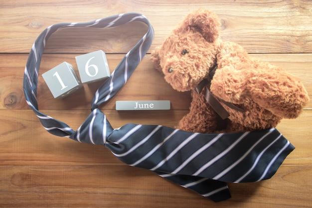 Calendário de madeira vintage para 16 de junho com ursinho de pelúcia e gravata inscripti feliz dia dos pais