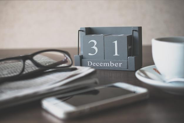 Calendário de madeira vintage para dia 31 de dezembro na mesa de escritório com óculos de leitura de jornal