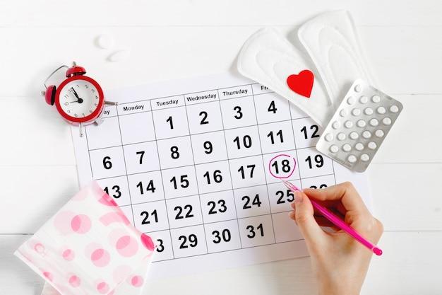 Calendário de menstruação com almofadas, despertador, pílulas anticoncepcionais hormonais. conceito de ciclo menstrual da fêmea. analgésicos para dor menstrual