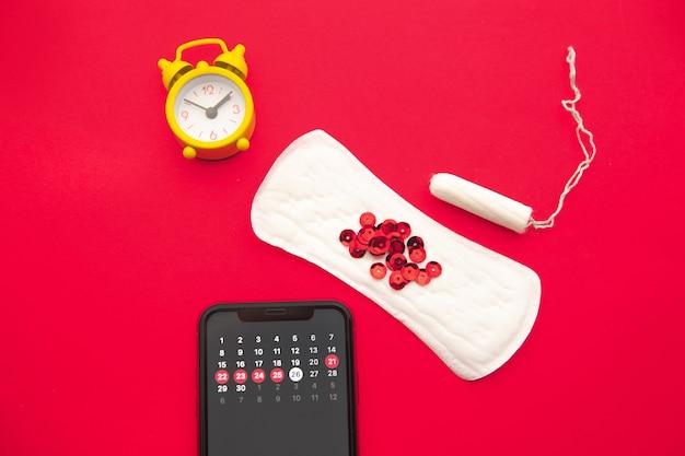 Calendário de menstruação em smartphone com tampão de algodão